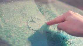 Een mooie vrouwelijke hand trekt een symbool van de hartvorm op de bevroren autovoorruit die met sneeuw op St Valentine Dag wordt stock footage