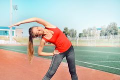 Een mooie vrouwenatleet die haar lichaam uitrekken bij stadionspoor Royalty-vrije Stock Afbeelding