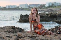 Een mooie vrouwenzitting op de het strand en het drinken wijn Stock Fotografie