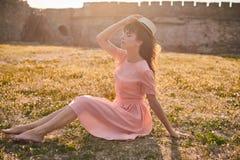 Een mooie vrouwenzitting op het gras met achtergrond van de kasteelmuren stock foto's