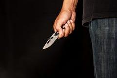 Een moordenaarspersoon met scherp stock afbeeldingen
