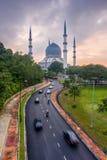 Een moskee en een bewolkte zonsopgang met auto's die zich op wegen bewegen Stock Foto's