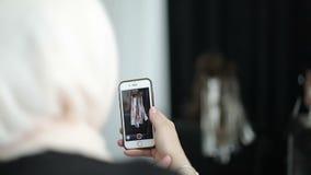 Een Moslimdievrouw in een sjaal maakt een video op een mobiele telefoon op masterclass voor haarkleuring en kapper` s art. wordt  stock footage