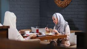 Een moslimvrouwenzitting in een koffie die hun schotels en het spreken eten stock footage
