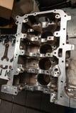 Een motor met vier cilinders veinste en verwijderde uit auto op een werkbank in een workshop van de voertuigreparatie De autoindu stock foto's