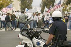 Een motorfietspolitieagent bekijkt protesteerders tegen George W Bush en de oorlog van Irak bij een Oorlog anti-Irak protesteren  Stock Foto