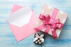 Een multi-colored envelop met een inschrijvingsbriefhoofd en een giftvakje op een blauwe houten lijst Hoogste mening stock fotografie