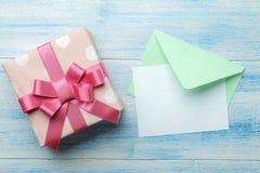 een multi-colored envelop met een inschrijvingsbriefhoofd en een giftvakje op een blauwe houten lijst Hoogste mening stock foto's