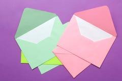 Een multi-colored envelop met een spatie voor een inschrijving op een heldere in lilac achtergrond Hoogste mening royalty-vrije stock fotografie