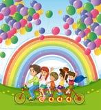Een multi-gereden fiets onder de drijvende ballons dichtbij rainbo Royalty-vrije Stock Afbeeldingen