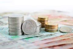 Een muntstuk met het symbool van de roebel op de achtergrond van stapels muntstukken en bankbiljetten Royalty-vrije Stock Afbeeldingen