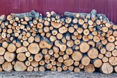 Een muur van gestapeld die brandhout voor de wintertijd voor het verwarmen van een huis en een sauna wordt geoogst stock fotografie