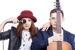 Een muzikaal duo van jongelui koppelt, een zanger in een rode hoed aan een mi royalty-vrije stock afbeeldingen
