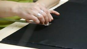 Een naaister die een hoogte snijden - de zwarte van de kwaliteitsstof, alvorens u het naait en een stuk van hoge manierkleding ma stock footage