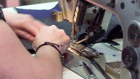 Een naaister naait doeken in de productielijn van het stoffenatelier Sluit omhoog van een naaimachine stock videobeelden