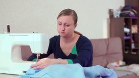 Een naaister thuis bij het verhaal die met een witte naaimachine werken Zij creeert nieuwe kleren stock videobeelden