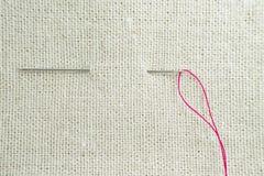 Een naald en een draad door de stof wordt getrokken die Royalty-vrije Stock Foto