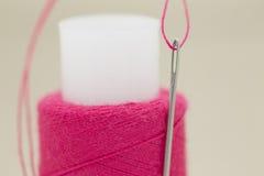 Een naald en een spoel van draad Stock Afbeelding