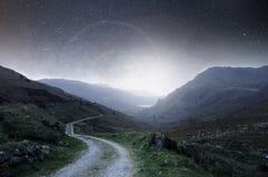 Een nachtconcept geeft uit Een rubriek van het bergspoor in de afstand bij nacht met sterren in de hemel met een helder licht die royalty-vrije stock afbeelding