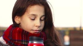 Een nadenkend meisje drinkt een warme drank van een hete mok stock footage