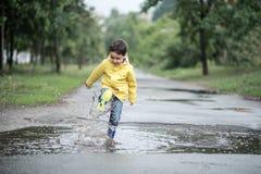 Een nat kind springt in een vulklei pret op de straat Het aanmaken in de zomer stock afbeelding