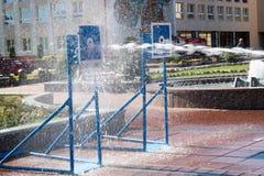 Een natte, krachtige stroom van waterplonsen en spruiten bij het doel, met heel wat druk op de straat bij de aantrekkelijkheid stock foto