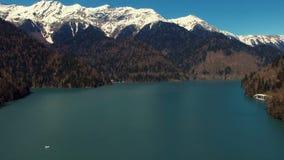 Een natuurlijk landschap, een mening van de snow-capped bergen, een blauw meer en bomen stock footage