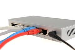 Een netwerkschakelaar is verbonden gekleurde kabels Royalty-vrije Stock Afbeeldingen