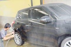 Een niet geïdentificeerde Aziatische mens die een auto wassen Stock Afbeelding