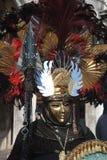 Een niet geïdentificeerde mens en kleding gedetailleerde kostuums met gouden maskers, rode en zwarte veerhoed tijdens Venetië Car Stock Afbeeldingen