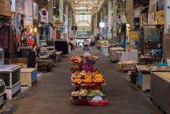 Een niet geïdentificeerde vrouw verkoopt vruchten en mushroons in Dongmun-Markt Royalty-vrije Stock Afbeeldingen