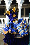Een niet geïdentificeerde mens in blauw en geel kostuum met masker, jokerhoed met rammelaars, blauwe ring en handschoenen tijdens Stock Afbeeldingen