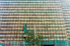 Een nieuw gebouw dat in aanbouw op achtergrond van een elektrostraatlantaarn is Stock Fotografie