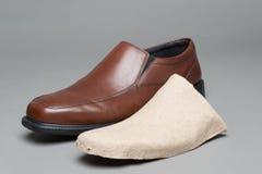 Een nieuwe die schoen en het kartontussenvoegsel wordt gebruikt om zijn vorm te bewaren stock foto