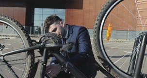 Een nieuwe fiets brak met een jonge zakenman in een kostuum stock videobeelden