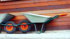 Een nieuwe grijze kruiwagen voor een houten muur stock foto's