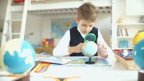 Een nieuwsgierige jongen die bol bestuderen Een schooljongen die aardrijkskunde bestuderen stock videobeelden