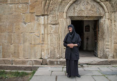 een non bij een deur van een oud klooster in Ananuri, Georgië Royalty-vrije Stock Afbeeldingen