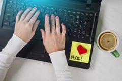 Een nota van tekst 14 02 geschreven op een document sticker Achtergrondcomputer, laptop, vrouwen` s handen op het toetsenbord Stock Foto