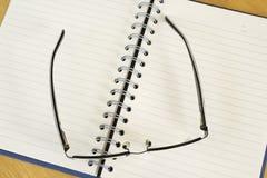 Een notitieboekje en glazen. Stock Fotografie