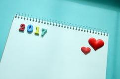 Een notitieboekje en harten op een blauwe achtergrond Stock Fotografie