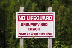 Een nr-gebruik van het badmeester unsupervised strand bij eigen risicoteken Stock Foto