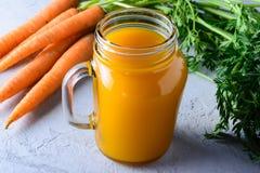 Een nuttige veggie drank Mooie samenstelling met groenten en kruik wortelsap Royalty-vrije Stock Foto