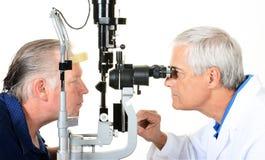 Een Oftalmoloog en een patiënt met een Spleetlamp stock foto's