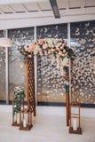 Een omvangrijke die huwelijksboog met bloemen, kandelaars en decoratieve vlinders wordt verfraaid Stock Afbeeldingen