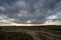 Een Onderbreking in de Wolken Somber landschap met het verre zon breken stock afbeelding