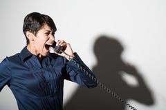 Een onderneemster die op de telefoon schreeuwen royalty-vrije stock afbeelding