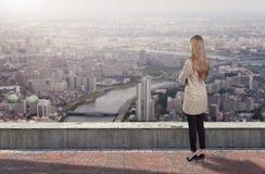 Een onderneemster die zich op dak bevinden die stad bekijken stock foto