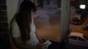 Een onderneemster zit op de vensterbank dichtbij een donker venster en werkt aan laptop stock videobeelden