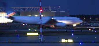 Een onduidelijk beeld van de vliegtuig beginnend snelheid bij een luchthaven bij nacht Stock Foto